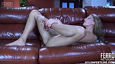 Slender blonde Fiona lies on couch sensually massaging her feet and sucking her toes
