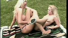 Skinny blonde lesbians use their strap-ons to play together outdoors